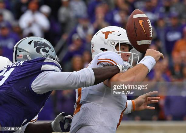 Quarterback Sam Ehlinger of the Texas Longhorns fumbles the ball after getting hit from behind by defensive end Reggie Walker of the Kansas State...