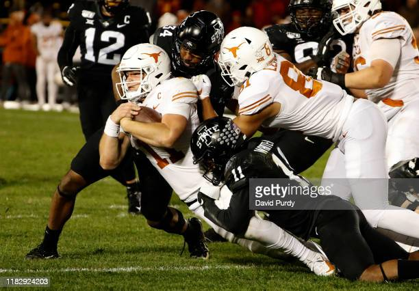 Quarterback Sam Ehlinger of the Texas Longhorns is tackled by linebacker O'Rien Vance and defensive back Lawrence White of the Iowa State Cyclones as...