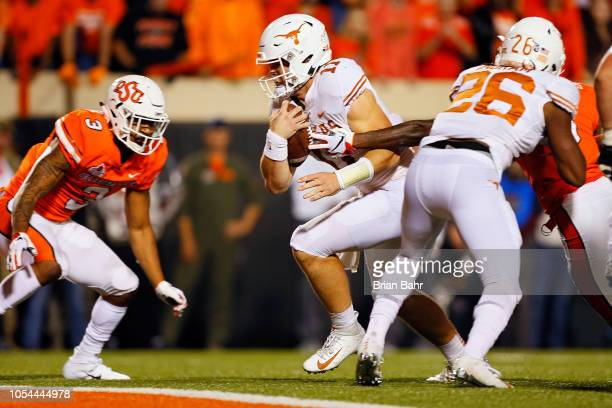 Quarterback Sam Ehlinger of the Texas Longhorns slips into the end zone for a touchdown with five yard carry against linebacker Kenneth...