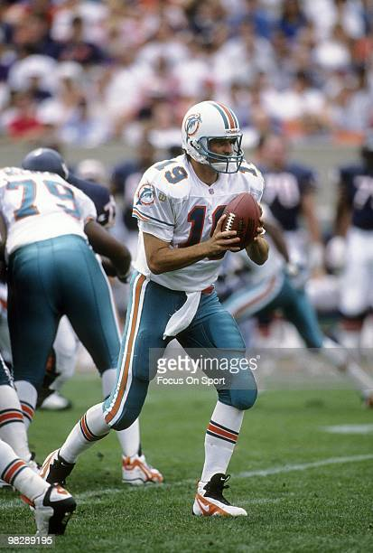 Quarterback Scott Mitchell of the Miami Dolphins turns to hand the ball off to a running back against the Chicago Bears during an NFL football game...