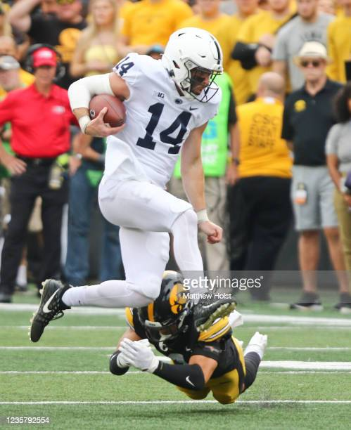 Quarterback Sean Clifford of the Penn State Nittany Lions leaps during the first half over defensive back Dane Belton of the Iowa Hawkeyes at Kinnick...