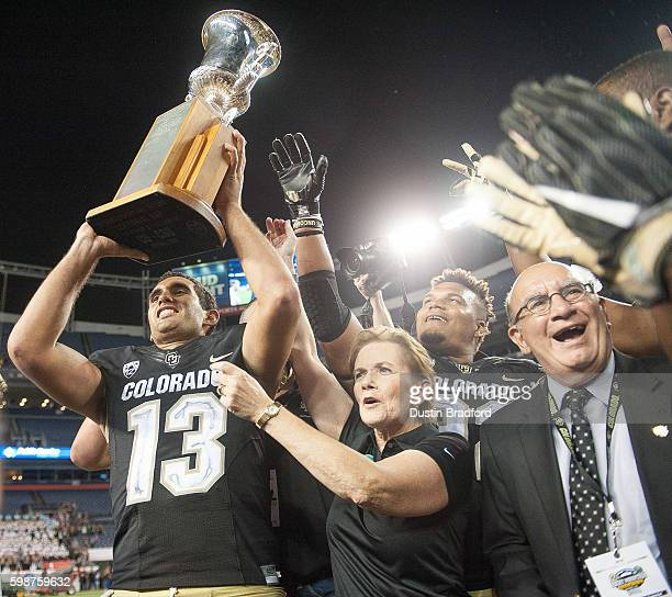 Quarterback Sefo Liufau of the Colorado Buffaloes hoists the Centennial Trophy after defeating the Colorado State Rams at Sports Authority Field at...