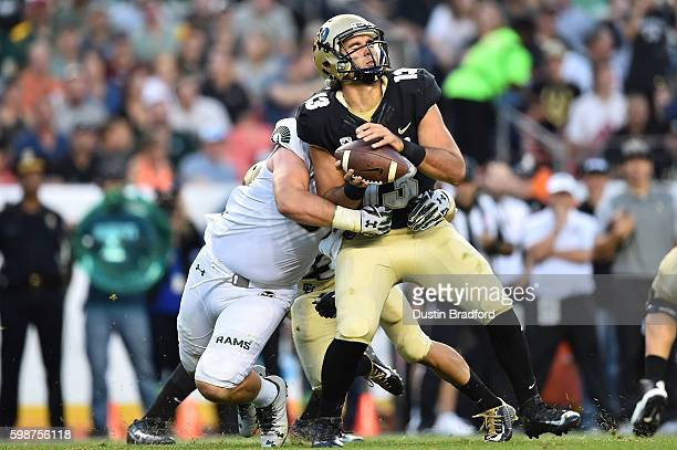Quarterback Sefo Liufau of the Colorado Buffaloes is hit by defensive lineman Jakob Buys of the Colorado State Rams for a sack in the first half of a...