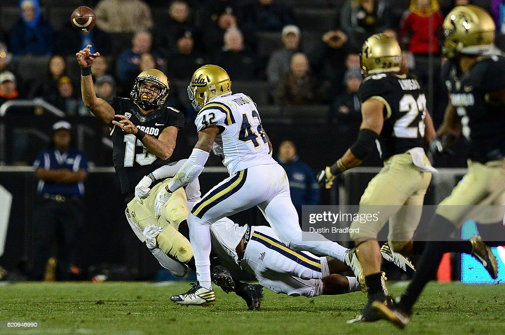 Quarterback Sefo Liufau #13 of the Colorado Buffaloes passes to running back Phillip Lindsay #23 as he is tackled during a game against the UCLA Bruins at Folsom Field on November 3, 2016 in Boulder, Colorado.