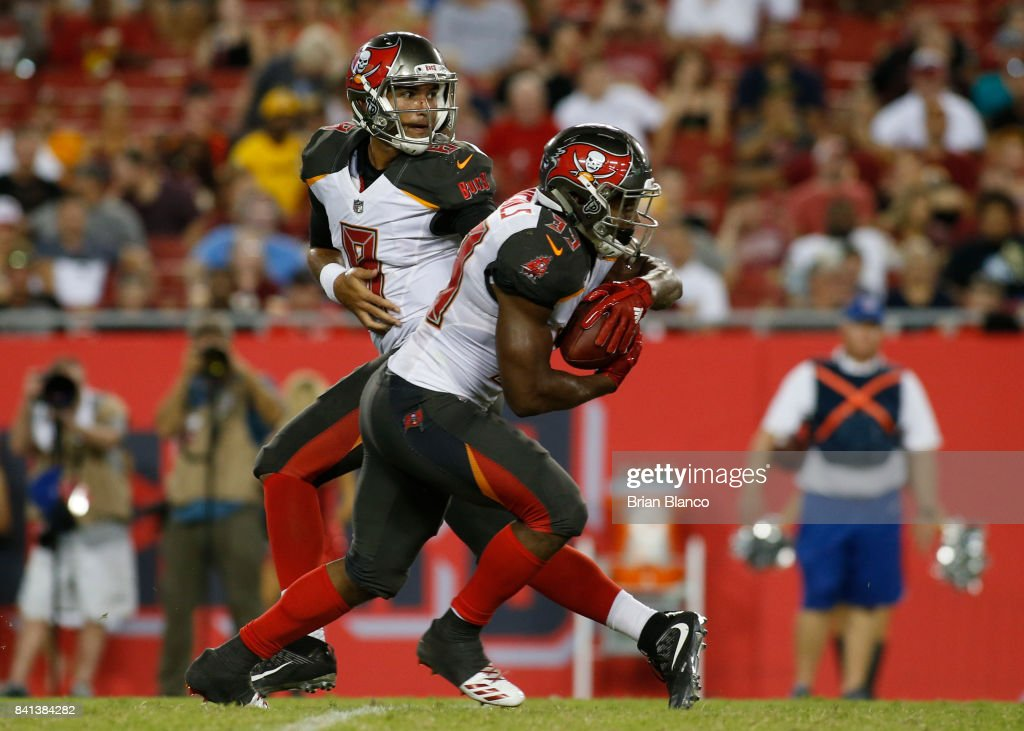 Quarterback Sefo Liufau #8 of the Tampa Bay Buccaneers ands off to running back Jeremy McNichols #33 during the third quarter of an NFL preseason football game against the Washington Redskins on August 31, 2017 at Raymond James Stadium in Tampa, Florida.