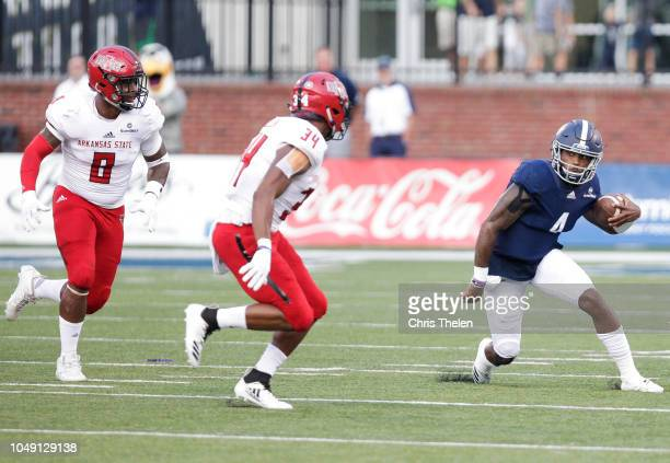 Quarterback Shai Werts of the Georgia Southern Eagles runs the ball during the first quarter as Darreon Jackson and Ronheen Bingham of the Arkansas...