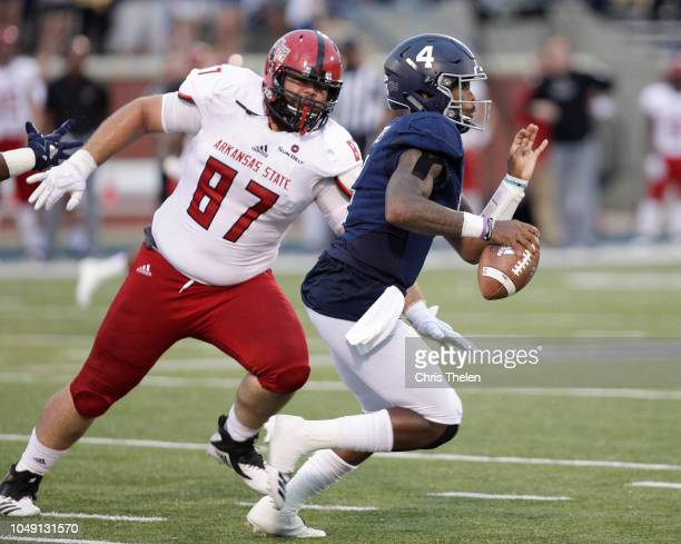 Quarterback Shai Werts of the Georgia Southern Eagles runs the ball as Javier Carbonell of the Arkansas State Red Wolves gives chase in the second...