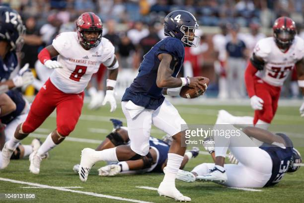 Quarterback Shai Werts of the Georgia Southern Eagles runs the ball as Ronheen Bingham of the Arkansas State Red Wolves gives chase in the second...