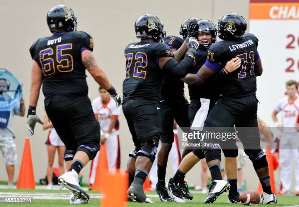 Quarterback Shane Carden of the East Carolina Pirates celebrates after scoring the game winning touchdown against the Virginia Tech Hokies at Lane...