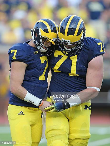 Quarterback Shane Morris of the Michigan Wolverines is helped off the field by Ben Braden during the fourth quarter of the game against the Minnesota...