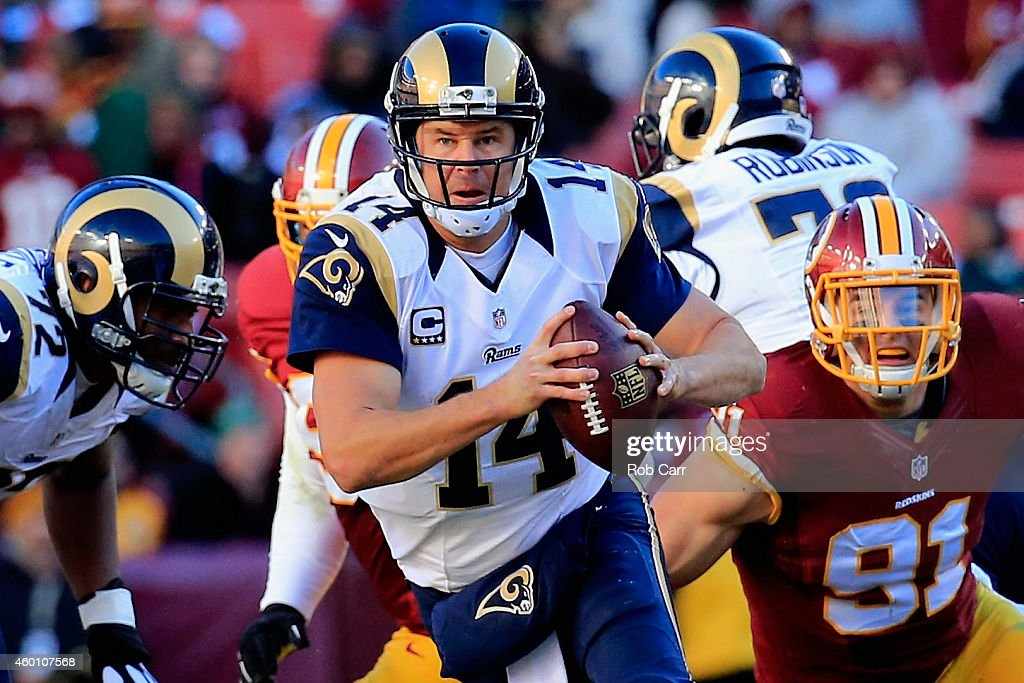 Quarterback Shaun Hill #14 of the St. Louis Rams scrambles to avoid the pressure of outside linebacker Ryan Kerrigan #91 of the Washington Redskins in the second quarter of a game at FedExField on December 7, 2014 in Landover, Maryland.