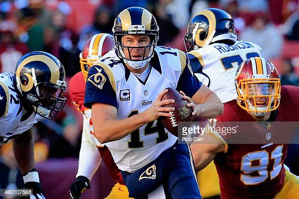 Quarterback Shaun Hill of the St. Louis Rams scrambles to avoid the pressure of outside linebacker Ryan Kerrigan of the Washington Redskins in the...