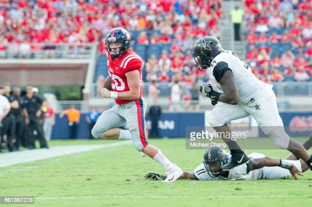 Quarterback Shea Patterson of the Mississippi Rebels runs the ball by linebacker Charles Wright of the Vanderbilt Commodores and defensive end Dare...