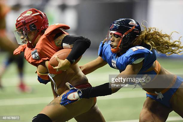 Quarterback Sindy Cummings of the Las Vegas Sin avoids a tackle by Chantell Taylor of the Chicago Bliss during their game at the Thomas Mack Center...