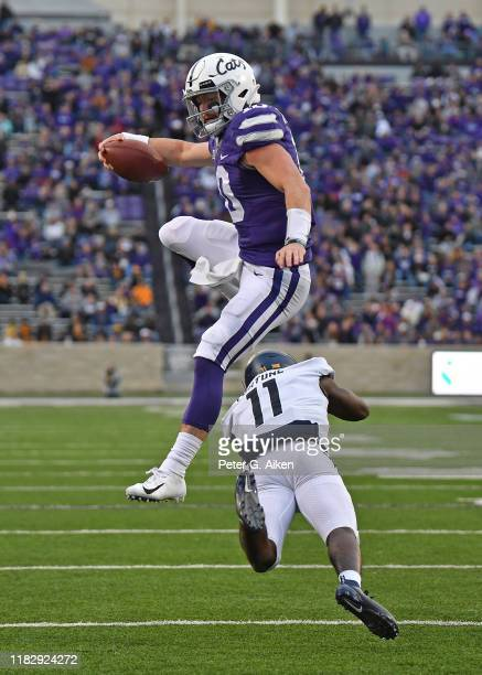 Quarterback Skylar Thompson of the Kansas State Wildcats leaps over cornerback Nicktroy Fortune of the West Virginia Mountaineers for extra yardage...