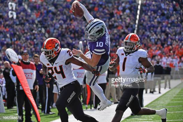 Quarterback Skylar Thompson of the Kansas State Wildcats makes a leaping attempt for the end zone between safety Jarrick Bernard and linebacker...