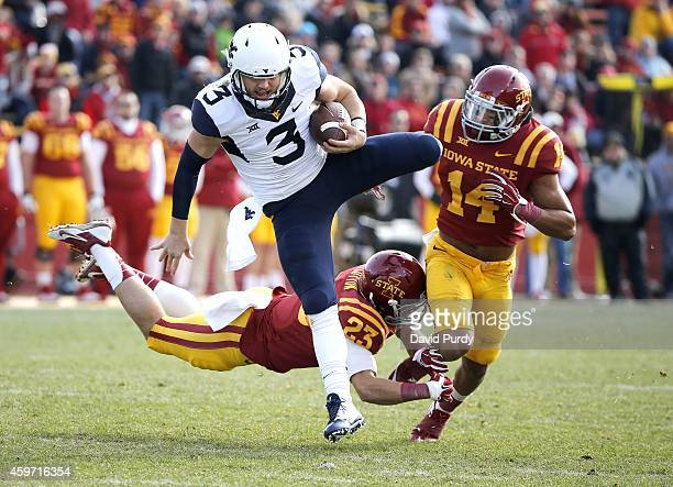 Quarterback Skyler Howard of the West Virginia Mountaineers jumps over defensive back Darian Cotton of the Iowa State Cyclones and linebacker Jared...