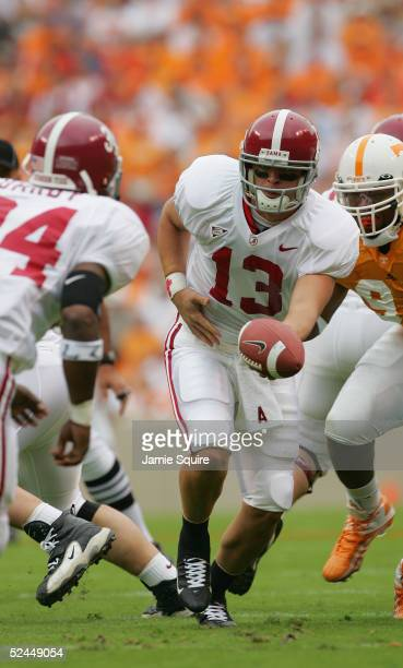 Quarterback Spencer Pennington of the Alabama Crimson Tide looks to handoff the ball to running back Kenneth Darby while playing the Tennessee...