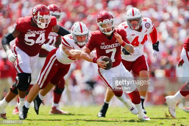 Quarterback Spencer Rattler of the Oklahoma Sooners scrambles for a first down against inside linebacker Luke Reimer and outside linebacker Garrett...