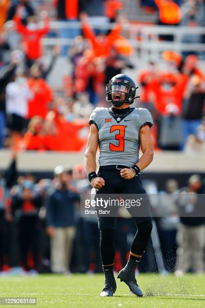 Quarterback Spencer Sanders of the Oklahoma State Cowboys celebrates after throwing a 34-yard touchdown to tight end Jelani Woods against the Iowa...
