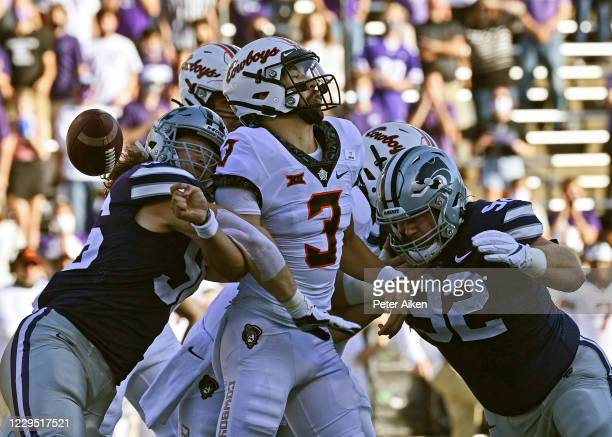 Quarterback Spencer Sanders of the Oklahoma State Cowboys fumbles the ball after getting hit by defensive end Wyatt Hubert of the Kansas State...