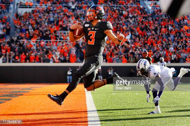 Quarterback Spencer Sanders of the Oklahoma State Cowboys leaps into the end zone for a 43-yard touchdown against safety Keenan Reed of the TCU...