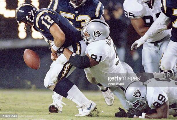 Quarterback Stan Humphries of the San Diego Chargers fumbles the ball as he is tackled by Chester McGlockton and Aundray Bruce of the Oakland Raiders...