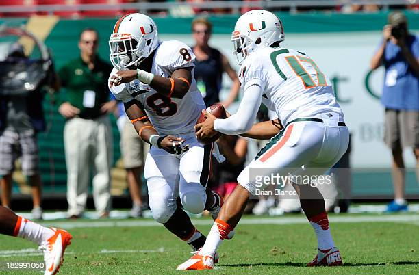 Quarterback Stephen Morris of the Miami Hurricanes fakes the hand off to running back Duke Johnson during the first quarter against the South Florida...