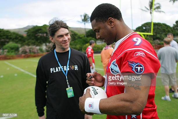 HONOLULU HI FEBRUARY 9 Quarterback Steve McNair of the AFC Tennessee Titans autographs a football for Al Evans winner of the PLAYERS INC NFL Players...