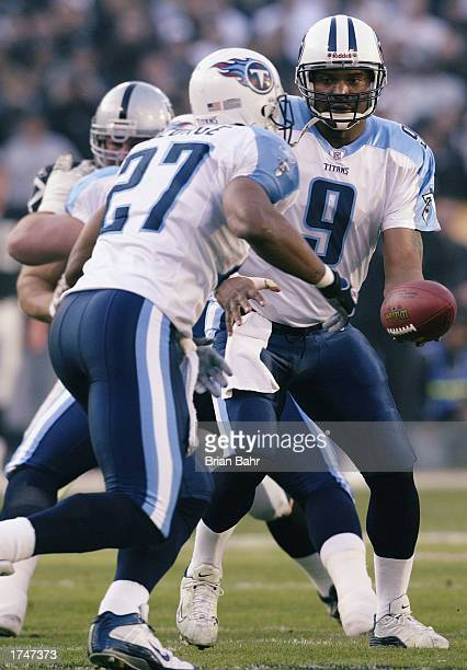 Quarterback Steve McNair of the Tennessee Titans motions for the handoff to runningback Eddie George during the AFC Championship game against the...