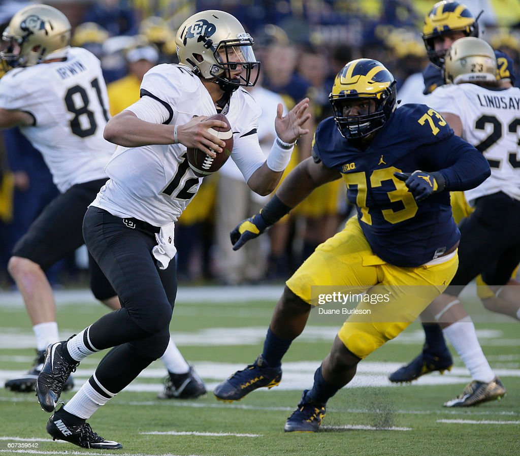Quarterback Steven Montez #12 of the Colorado Buffaloes is pursued by Maurice Hurst #73 of the Michigan Wolverine during the second half at Michigan Stadium on September 17, 2016 in Ann Arbor, Michigan. Michigan defeated Colorado 45-28.