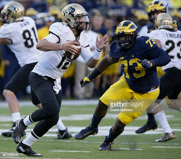 Quarterback Steven Montez of the Colorado Buffaloes is pursued by Maurice Hurst of the Michigan Wolverine during the second half at Michigan Stadium...