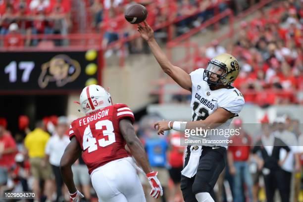 Quarterback Steven Montez of the Colorado Buffaloes passes over linebacker Tyrin Ferguson of the Nebraska Cornhuskers at Memorial Stadium on...