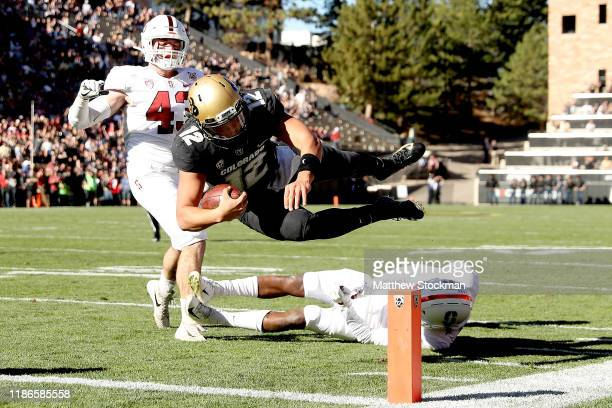 Quarterback Steven Montez of the Colorado Buffaloes scores a touchdown against Ryan Beecher and Paulson Abedo of the Stanford Cardinal in the first...