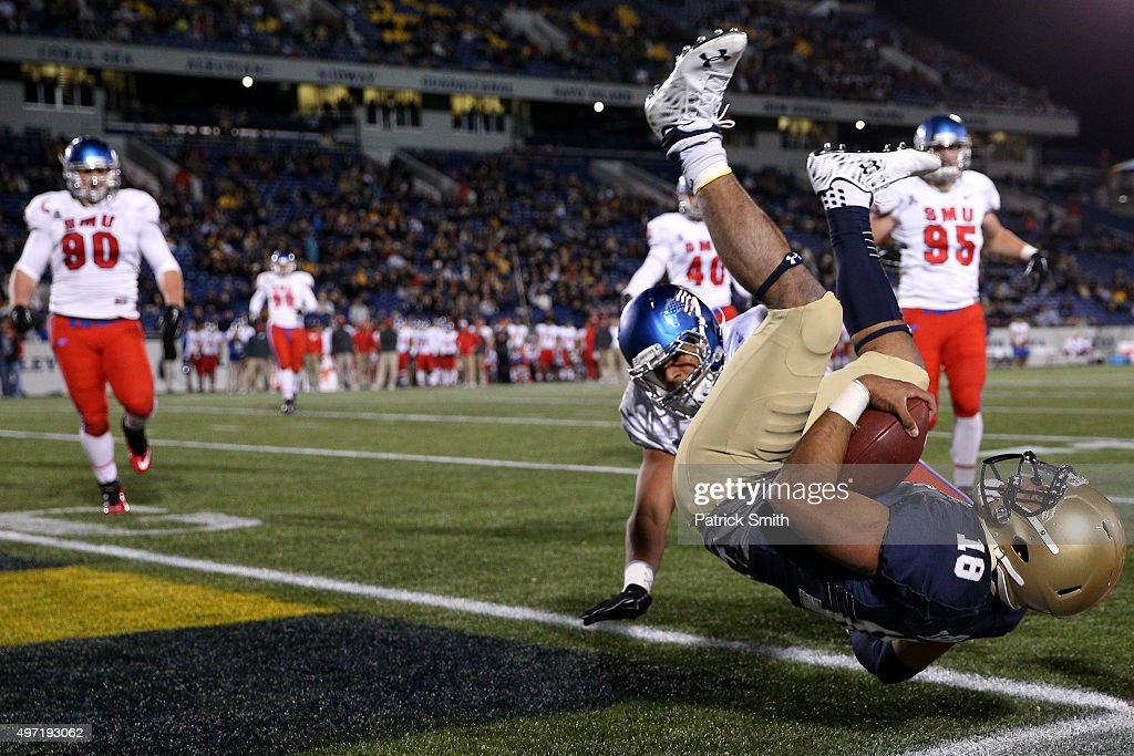 Quarterback Tago Smith #18 of the Navy Midshipmen scores a touchdown in front of Jackson Mitchell #44 of the Southern Methodist Mustangs in the fourth quarter at Navy-Marine Corps Memorial Stadium on November 14, 2015 in Annapolis, Maryland. The Navy Midshipmen won, 55-14.