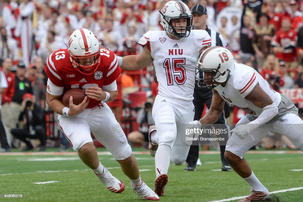 Quarterback Tanner Lee #13 of the Nebraska Cornhuskers avoids tackles from cornerback Shawun Lurry #19 of the Northern Illinois Huskies and defensive end Sutton Smith #15 at Memorial Stadium on September 16, 2017 in Lincoln, Nebraska.