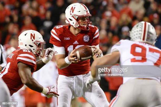 Quarterback Tanner Lee of the Nebraska Cornhuskers fields a snap against the Ohio State Buckeyes at Memorial Stadium on October 14 2017 in Lincoln...