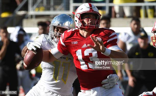 Quarterback Tanner Lee of the Nebraska Cornhuskers is stripped of the ball by cornerback Thomas Graham Jr #11 of the Oregon Ducks in the fourth...
