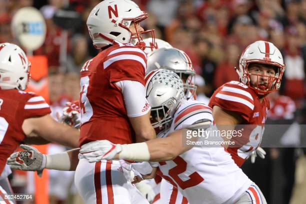 Quarterback Tanner Lee of the Nebraska Cornhuskers takes a hit from linebacker Tuf Borland of the Ohio State Buckeyes after throwing a pass at...