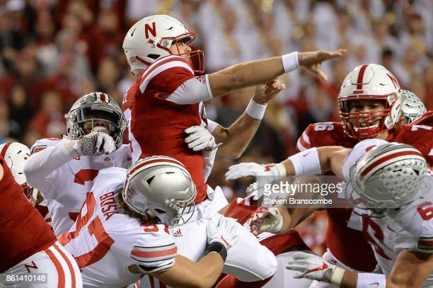 Quarterback Tanner Lee of the Nebraska Cornhuskers throws under pressure from defensive lineman Nick Bosa of the Ohio State Buckeyes at Memorial...