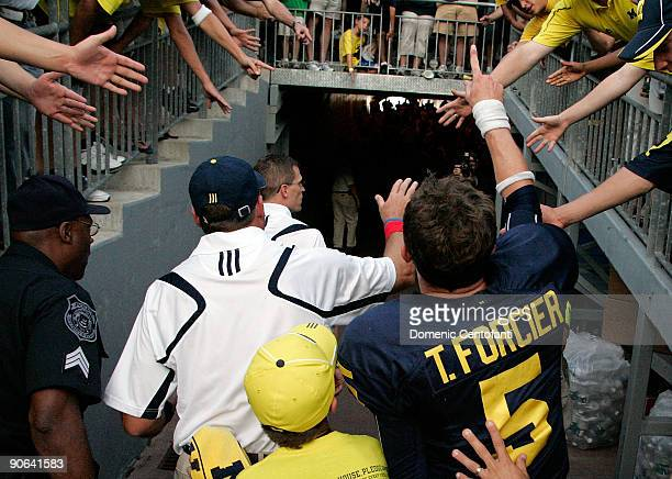 Quarterback Tate Forcier and Michigan head coach Rich Rodriguez give high-fives as they leave the field after beating Notre Dame 38-34 at Michigan...