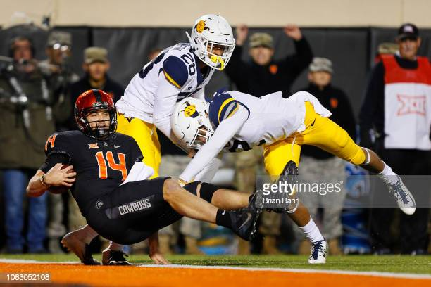 Quarterback Taylor Cornelius of the Oklahoma State Cowboys falls backward into the end zone for a touchdown against safety Kenny Robinson Jr #2 and...