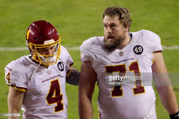 Quarterback Taylor Heinicke and offensive guard Wes Schweitzer of the Washington Football Team walk off the field together after losing to the Tampa...