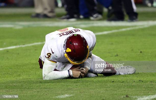 Quarterback Taylor Heinicke of the Washington Football Team grabs lies on the ground injured during the 4th quarter of the game against the Tampa Bay...