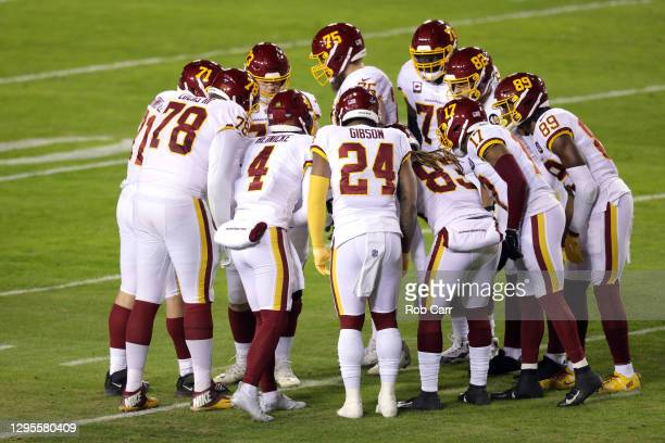 Quarterback Taylor Heinicke of the Washington Football Team huddles with the team during the first half of the NFC Wild Card playoff game against the...