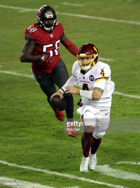Quarterback Taylor Heinicke of the Washington Football Team scrambles as outside linebacker Shaquil Barrett of the Tampa Bay Buccaneers chases during...