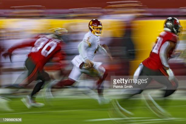Quarterback Taylor Heinicke of the Washington Football Team scrambles past outside linebacker Jason Pierre-Paul of the Tampa Bay Buccaneers during...