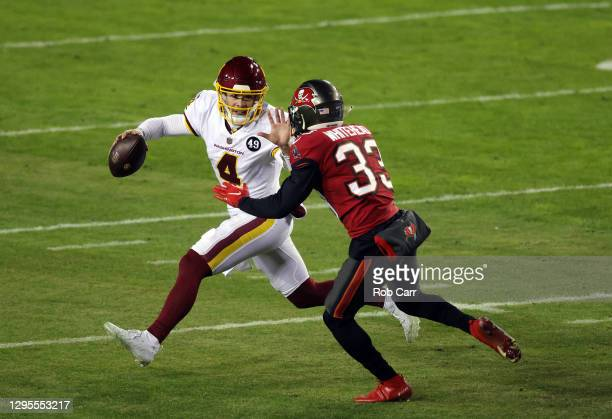 Quarterback Taylor Heinicke of the Washington Football Team rscrambles while being chased by free safety Jordan Whitehead of the Tampa Bay Buccaneers...