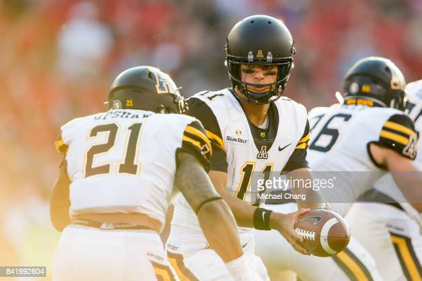 Quarterback Taylor Lamb of the Appalachian State Mountaineers looks to hand the ball off to running back Terrence Upshaw of the Appalachian State...