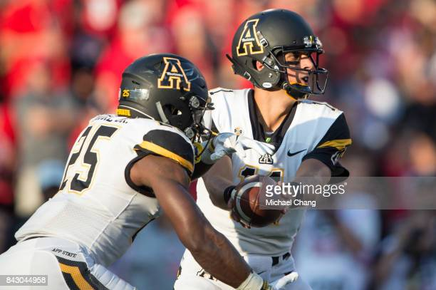 Quarterback Taylor Lamb of the Appalachian State Mountaineers looks to hand the ball off to running back Jalin Moore of the Appalachian State...